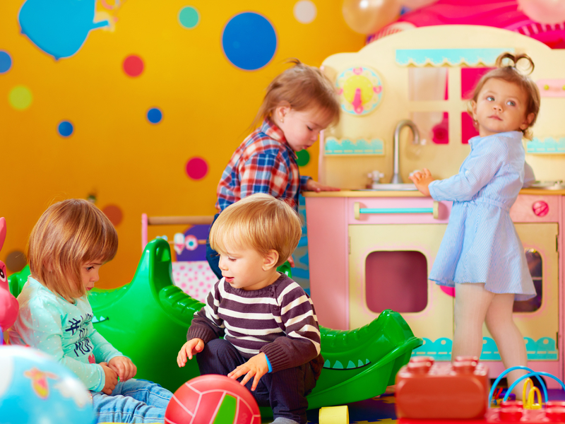 Quatre enfants en train de jouer dans une école maternelle.