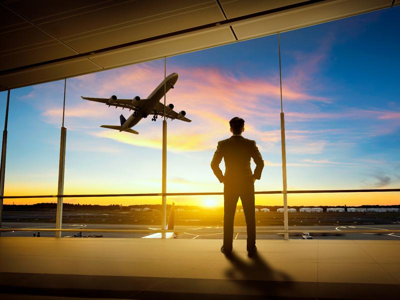 Un homme d'affaire regardant un avion s'envoler.