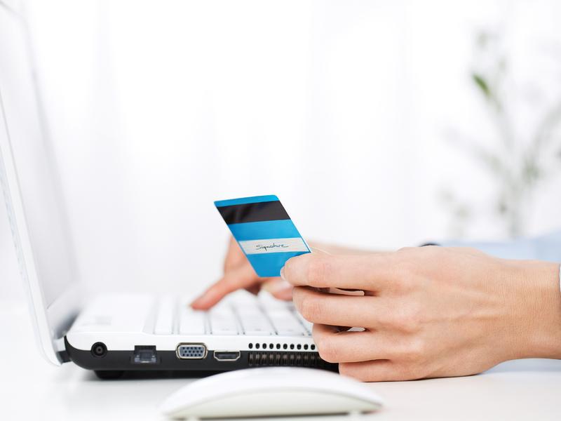Une personne qui paie une facture avec sa carte de crédit sur son ordinateur.