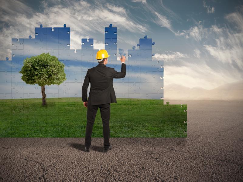 Un homme d'affaire avec un casque dans un désert ajoutant des pièces à un puzzle représentant un paysage vert avec un arbre.