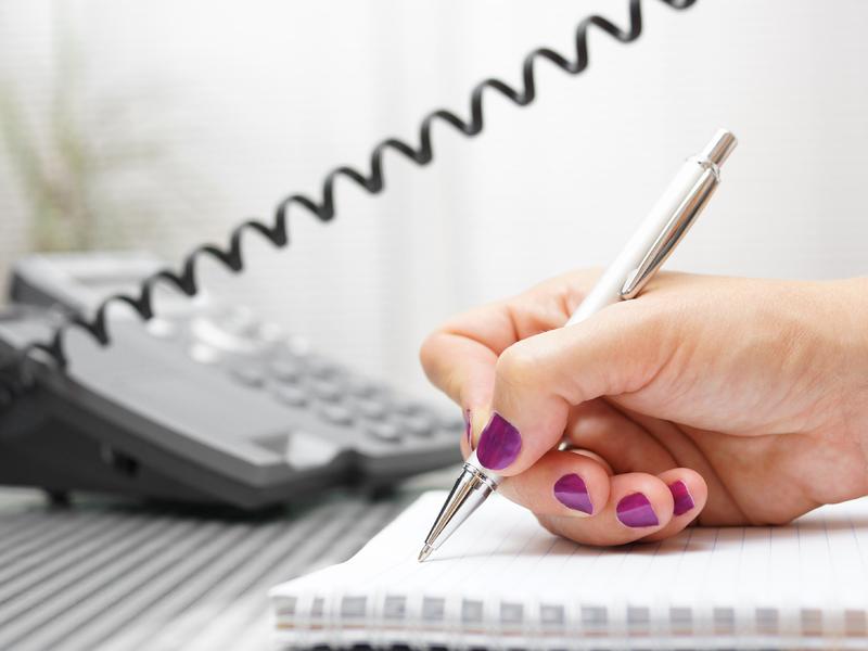 Une femme au téléphone qui prend des notes sur un calepin.