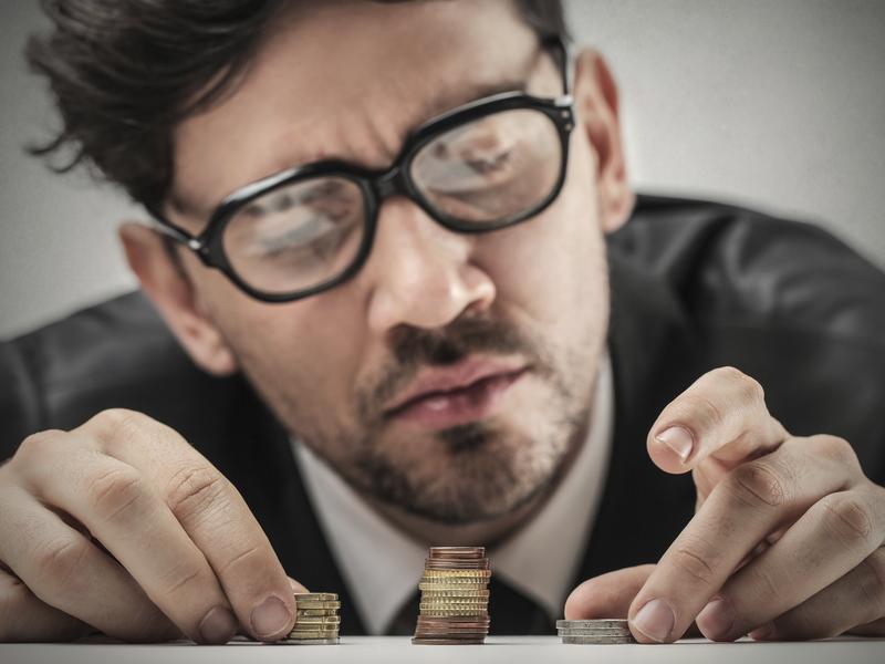 Un homme d'affaire avec des lunettes qui regarde trois petits tas d'argent de taille différente posés sur son bureau, avec circonscription.