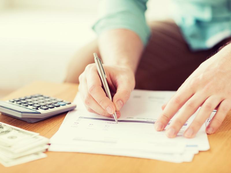 Une femme remplit des papiers fiscaux.