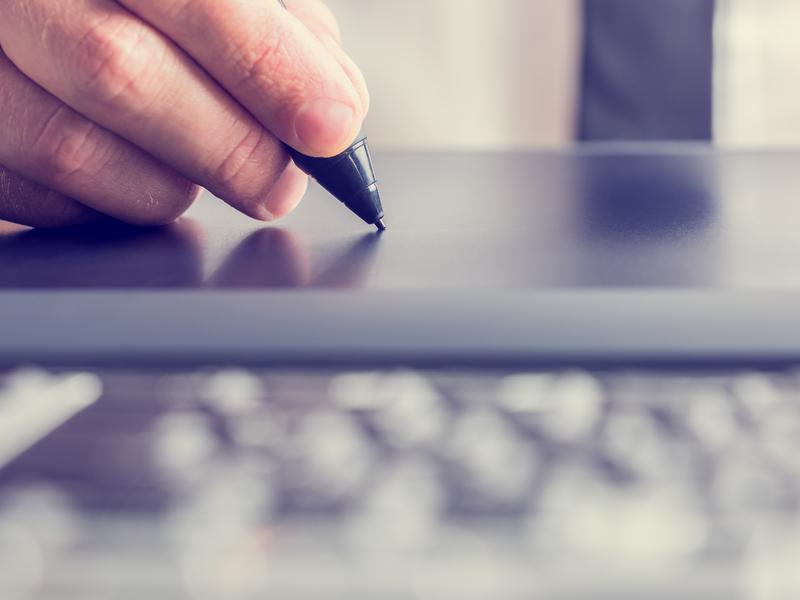 Un homme d'affaire signant sur une tablette électronique.