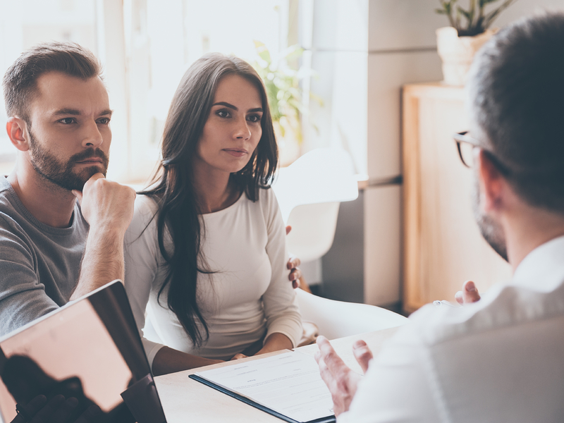Un couple concentré écoutant un conseiller financier.