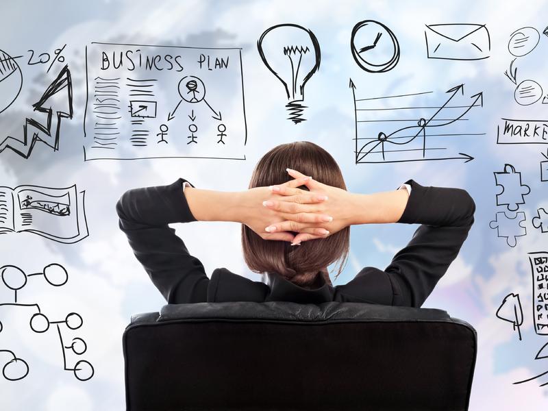 Une femme d'affaire assise regardant un tableau de plan de marché