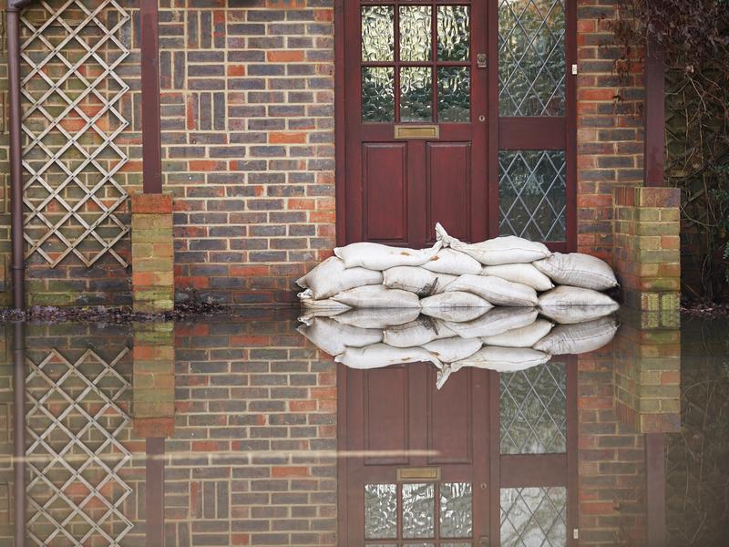 L'entrée d'une maison avec pleins de sacs de sable devant pour éviter qu'elle ne soit inondée.