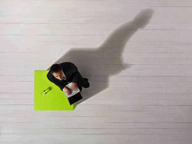 Un homme d'affaire attablé à une table verte avec son ordinateur. Son ombre est bien plus grande que lui.