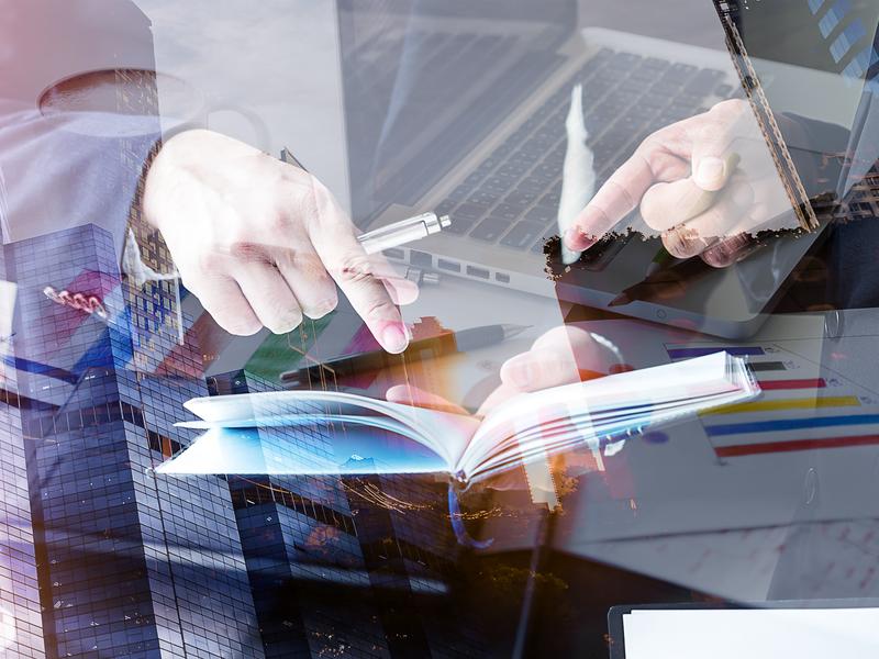 Deux hommes regardant un livre de compte en transparence, on voit un ordinateur avec des graphiques.