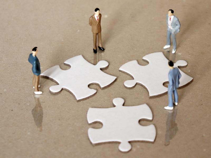 Quatre hommes d'affaires autour de trois pièce de puzzle, songeant à une fusion.