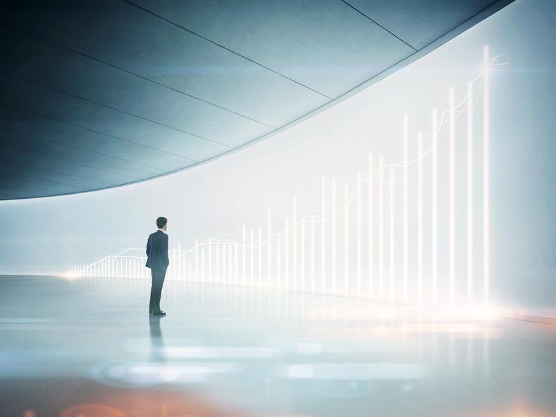 Un homme d'affaire devant un mur où on peut voir un graphique de croissance.