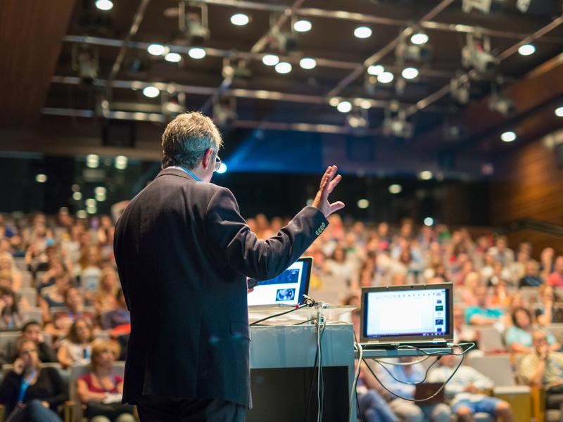 Un homme avec deux ordinateurs, sur une scène donnant une conférence devant une salle bondée.