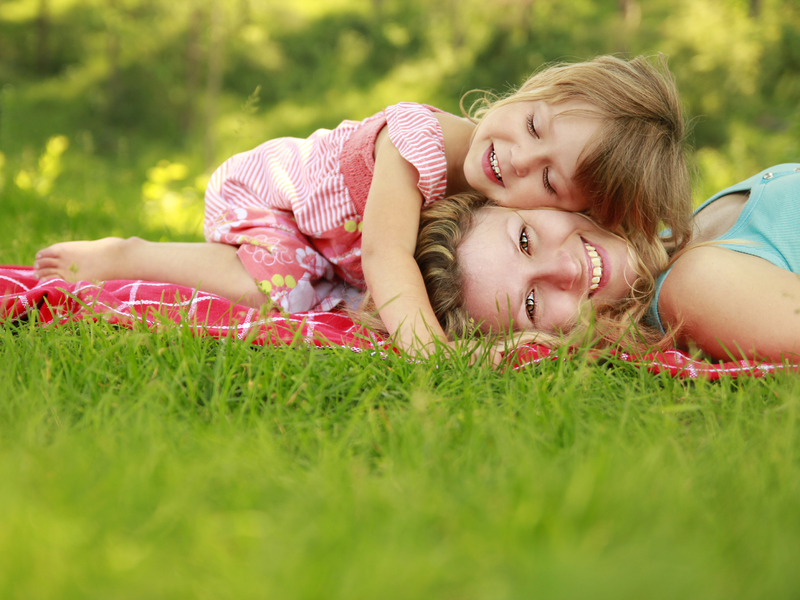 Une femme et sa fille allongée dans l'herbe.