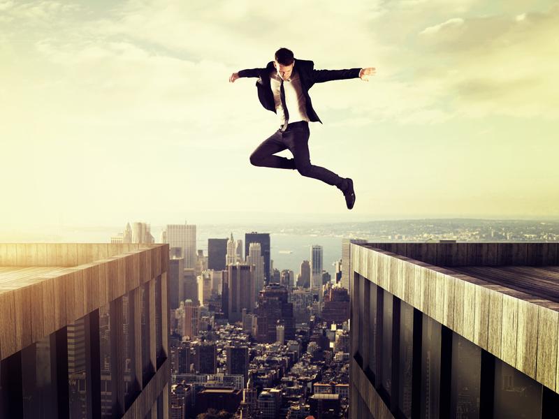 Un homme d'affaire sautant d'un toit sur un autre.
