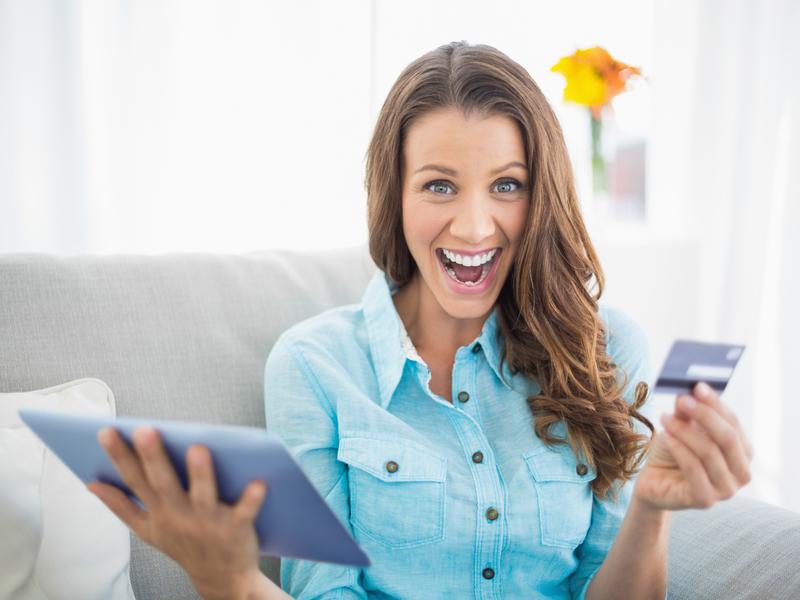 Une femme tenant une plaquette dans une main et une carte de crédit dans l'autre et qui semble euphorique.