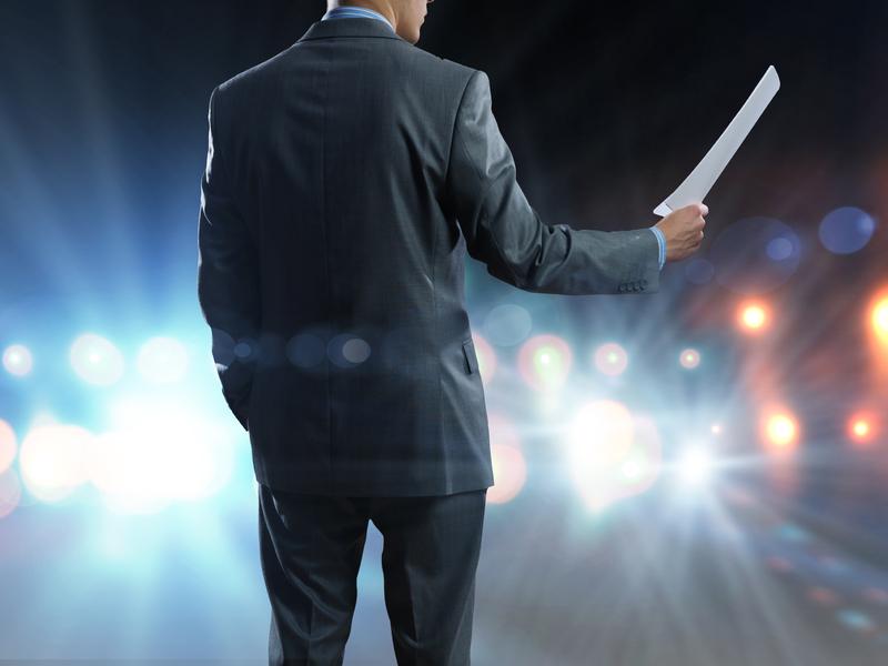 Un homme d'affaire avec un discours dans les mains sur une scène.