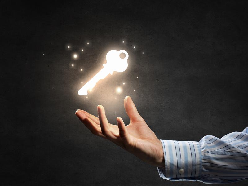 Un homme d'affaire présentant une clé phosphorescente qui flotte au-dessus de sa main.