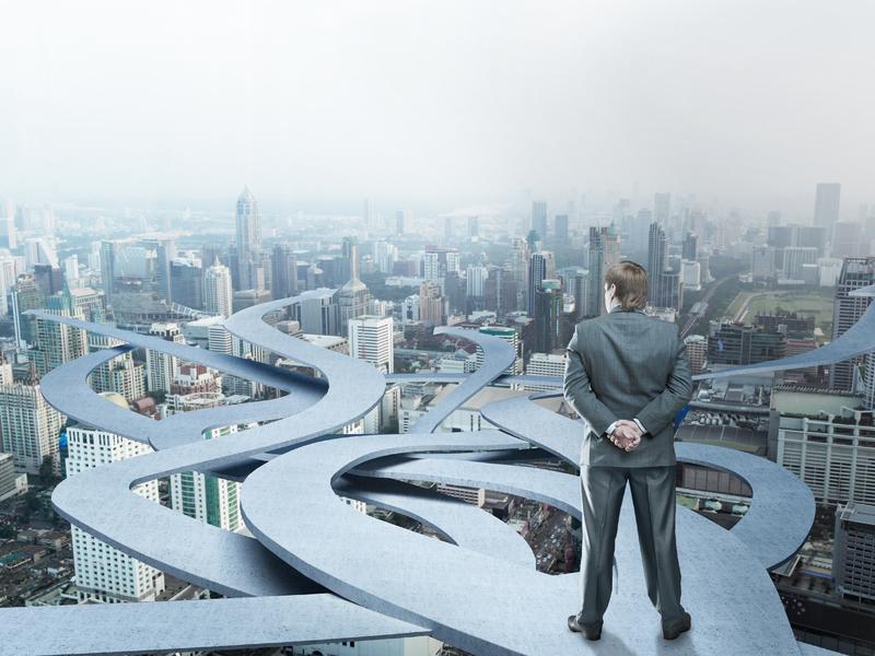 Un homme d'affaire devant pleins de routes au-dessus d'une ville.,