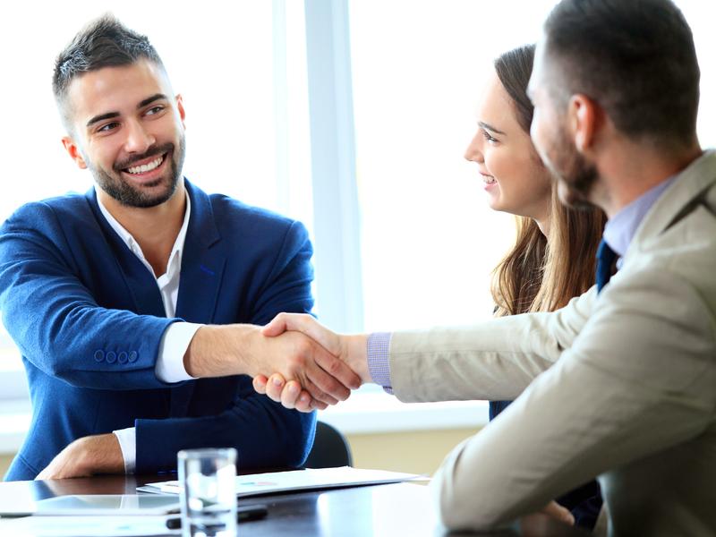 Un conseiller souriant avec un couple de clients.