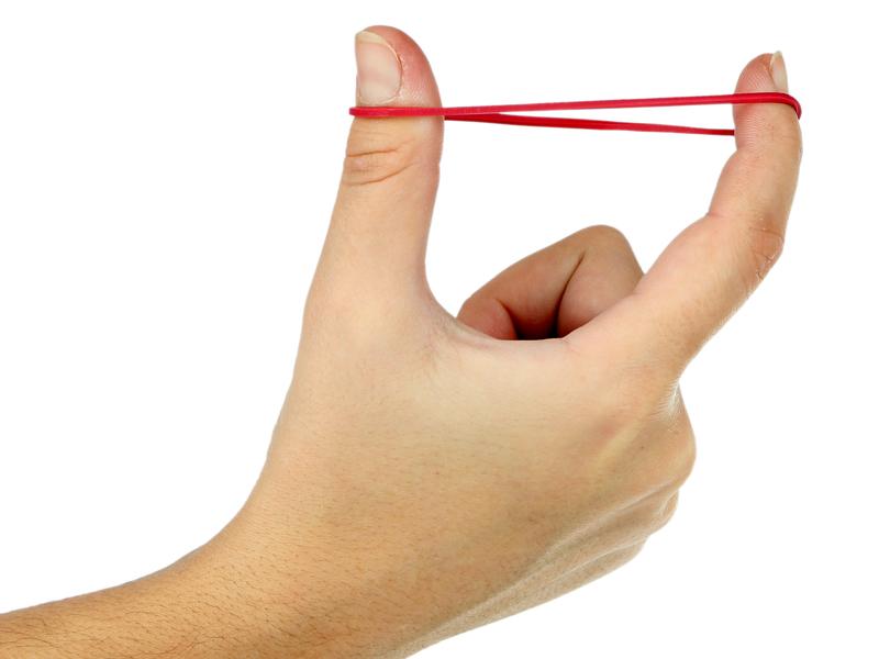Une main tenant un élastique entre deux doigts.