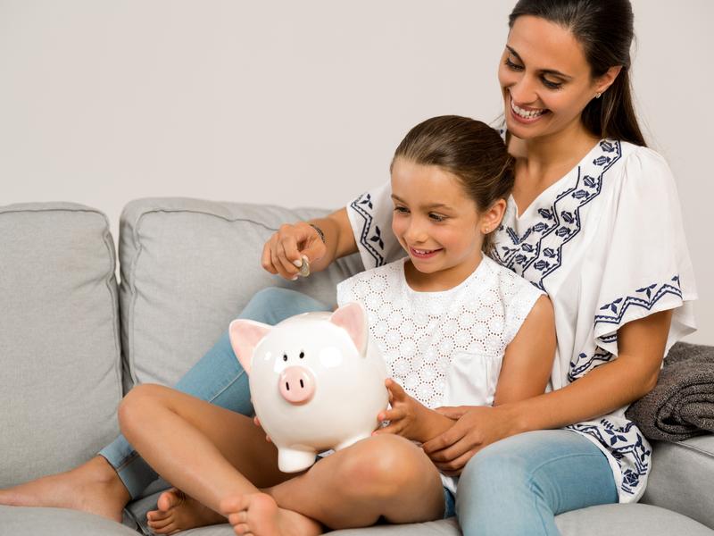 Une femme avec un enfant entre ses jambes assis sur un sofa. Elle met une pièce dans la tirelire sur les genoux de l'enfant.