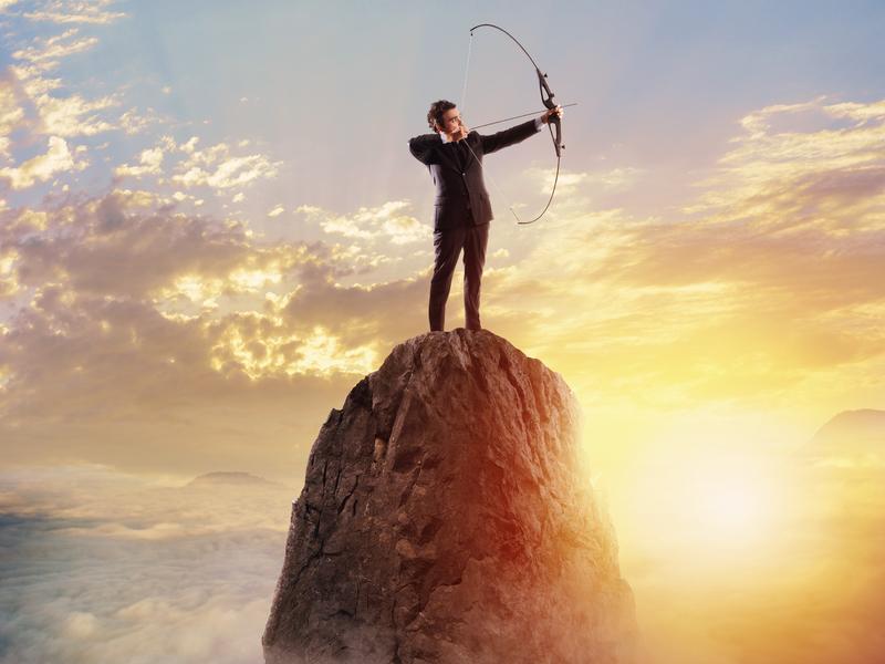 Un homme d'affaire en haut d'une montagne bandant un arc qu'il tient dans les mains devant un soleil couchant.