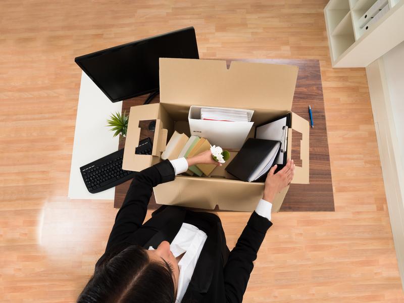 Femme d'affaire avec une boite dans les mains. Elle quitte son bureau.