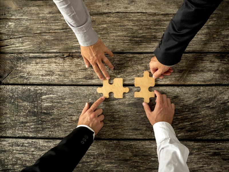 Quatre bras d'hommes d'affaire qui mettent ensemble deux pièces de puzzle.