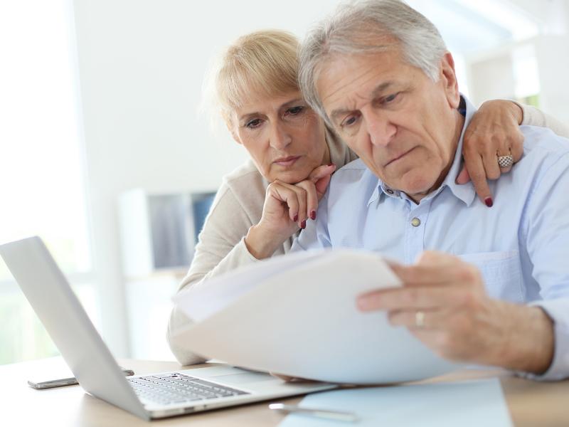 Un couple de personnes âgées devant un ordinateur lisant un document ensemble l'air soucieux.