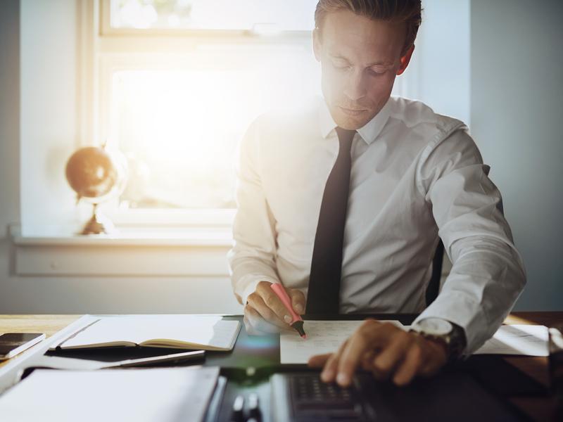 un comptable assis à un bureau. Il écrit sur des feuilles posés devant lui, son autre main pianote sur une calculatrice.