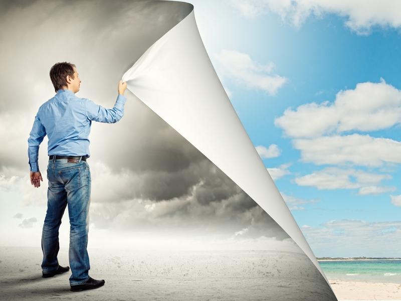 Un homme d'affaire arrachant un papier peint d'un ciel nuageux pour découvrir un ciel bleu et une plage.