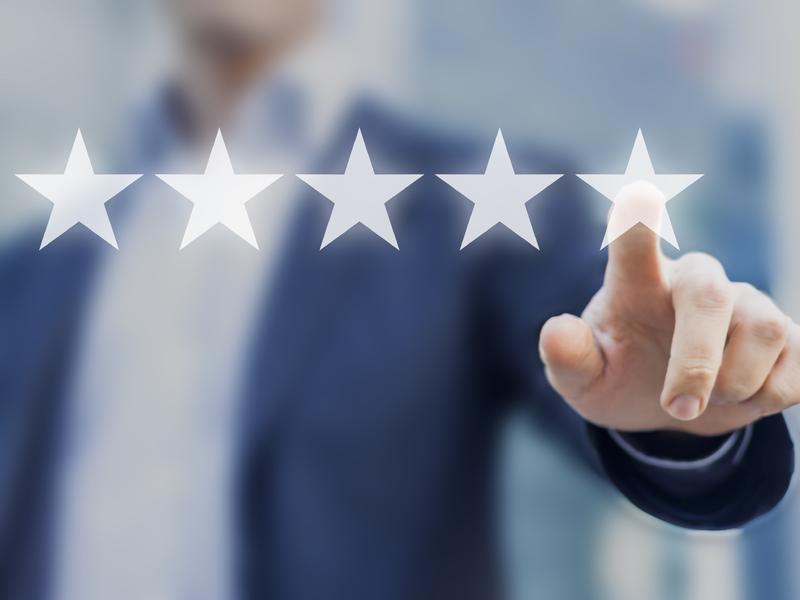 Un homme d'affaire posant son doigt sur une étoile, pour donner son appréciation.
