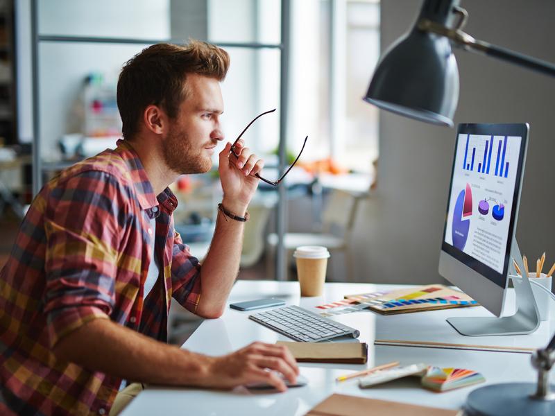 Un homme d'affaire à un bureau, l'air heureux devant un ordinateur lui présentant des graphiques.