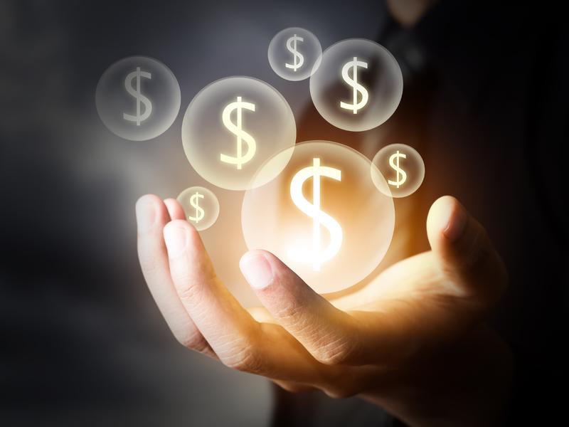 Un homme d'affaire avec la main tendue. Au-dessus, on voit pleins de bulles avec un signe d'argent dedans.
