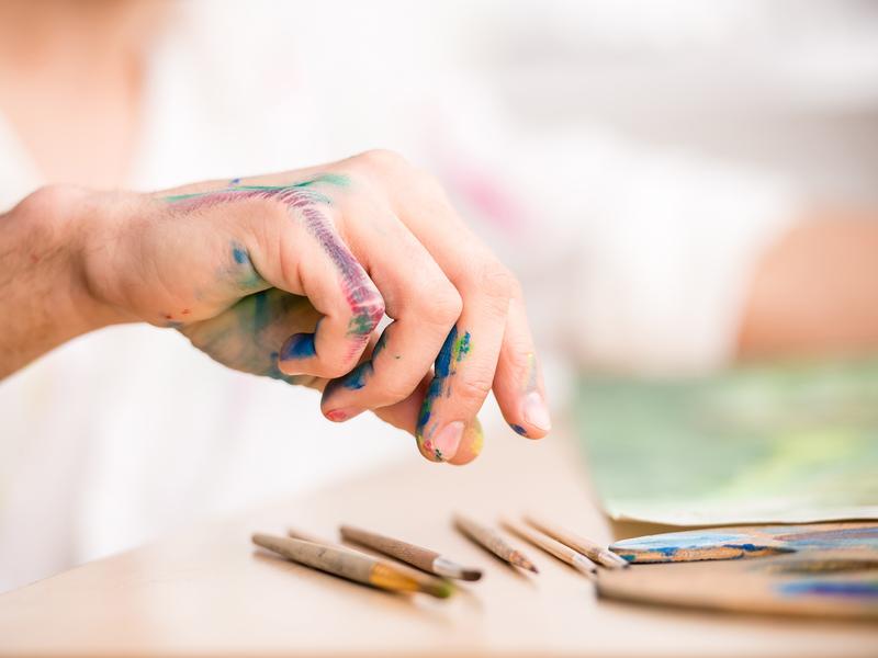 Une main pleine de peinture qui prend une aquarelle posée sur la table devant une feuille.