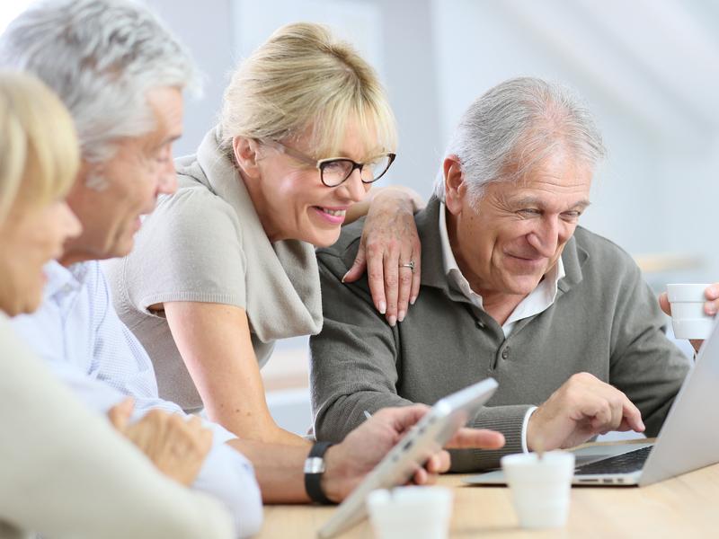 Deux couples de retraités qui ont l'air heureux et regardent un ordinateur.