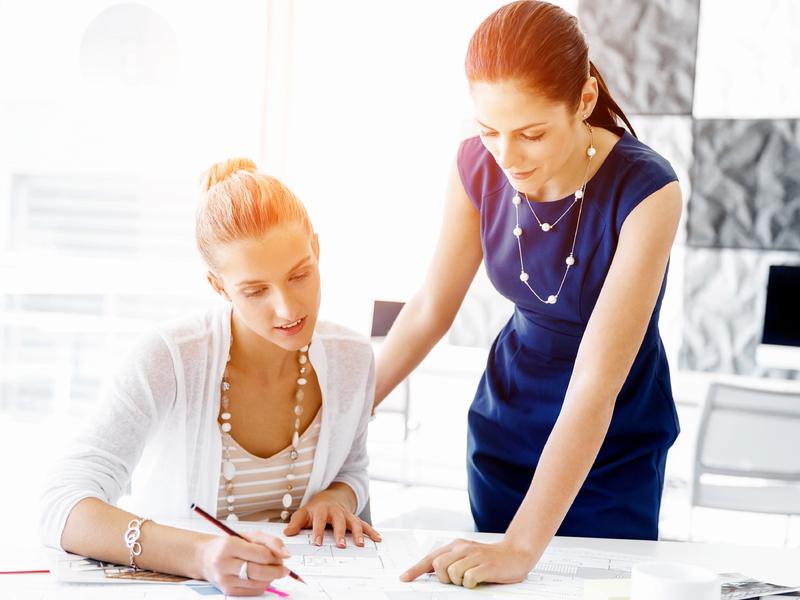 Deux femmes d'affaires devant une table, une assise, l'autre debout. Elles discutent d'un document.