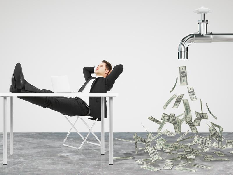 Un homme d'affaire assis sur une chaise, les jambes sur la table devant lui. Derrière on voit un robinet d'où coulent des billets de banque.