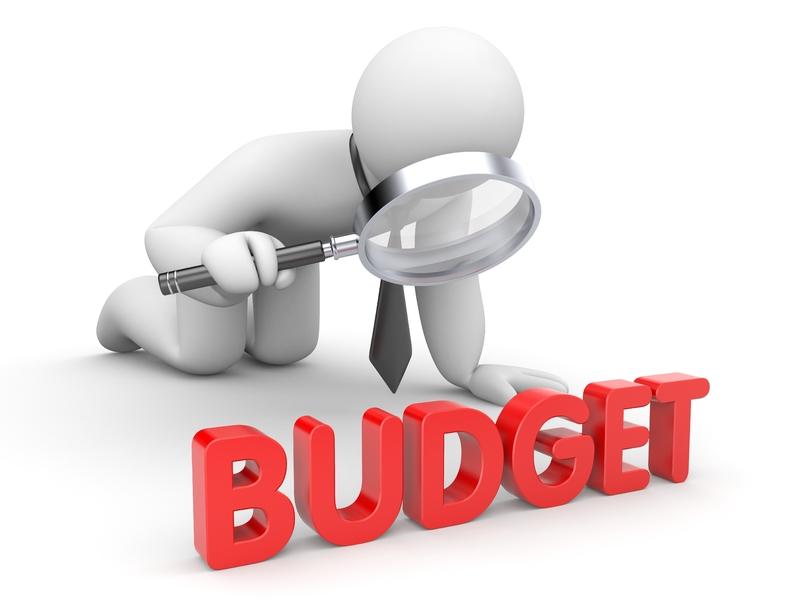 Un petit personnage avec une cravate et une loupe inspectant le mot Budget.
