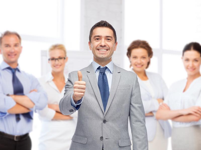 Un homme d'affaire le pouce en l'air, avec une équipe de quatre personnes derrière de femmes et d'hommes d'affaire heureux.