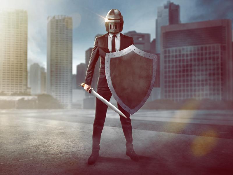 Un homme en costume d'affaires avec un casque de chevalier, un bouclier et une épée sur un fonds urbain.