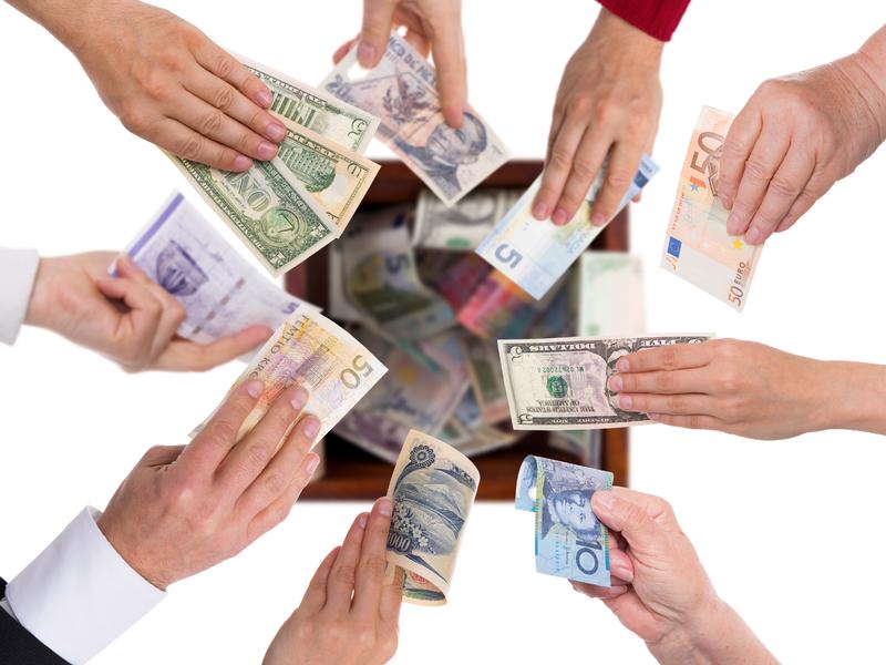 Des mains tendues en cercle. Dans chaque main on voit des billets de diverses pays.