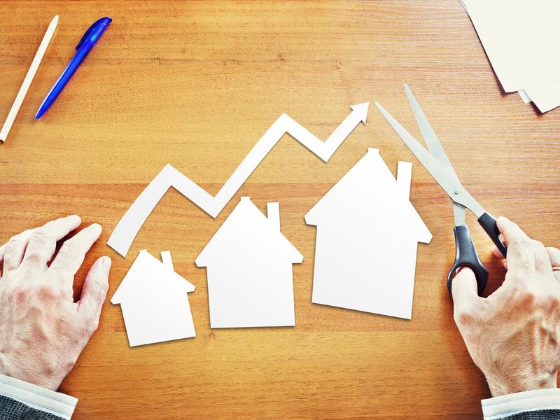 On voit simplement les mains d'un homme d'affaire avec des ciseaux, devant lui trois maisons en papier de plus en plus grandes posées sur une table. Au-dessus, une flèche également en papier montre la croissance.
