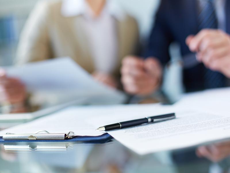 Des papiers et un stylo posé sur une table. Derrière on voit un homme et une femme d'affaire.