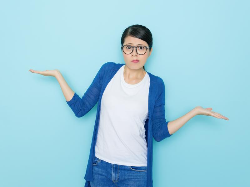 Une femme avec des lunettes qui hausse les épaules, ne sachant pas quoi choisir.