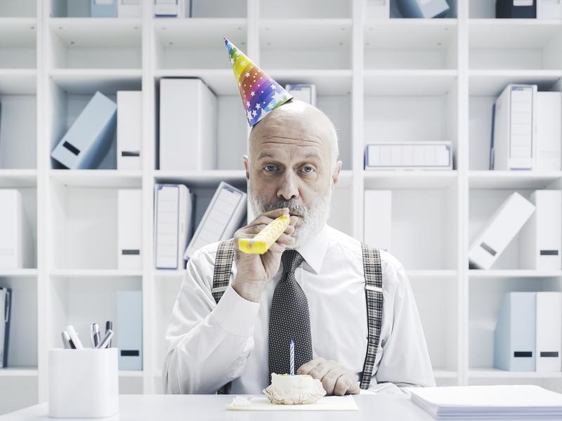 Un homme d'affaire avec un petit chapeau d'anniversaire et une trompette de fête, assis à un bureau devant un gâteau.