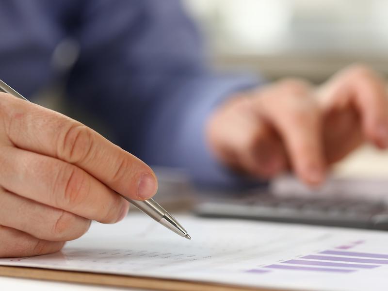 Un homme d'affaire à un bureau. On ne voit que ses mains. Il tient un style d'une main et écrit sur une calculette de l'autre.