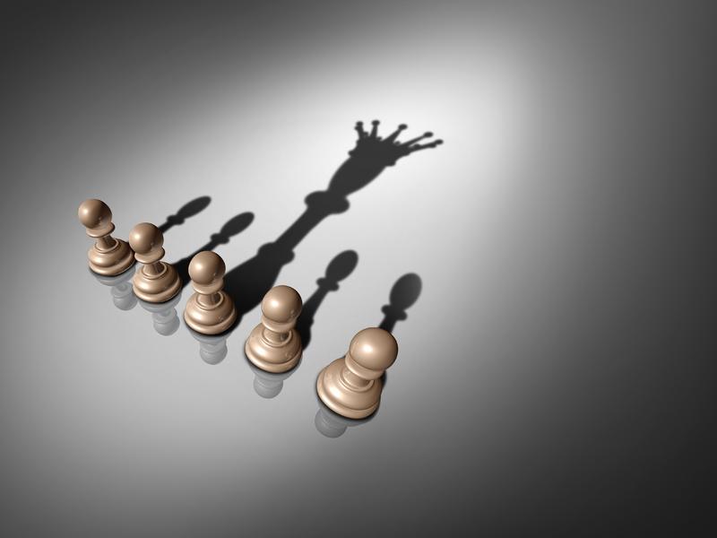 Cinq pions alignés sur un fond blanc. L'ombre de l'un des cinq est le roi et non un pion normal.