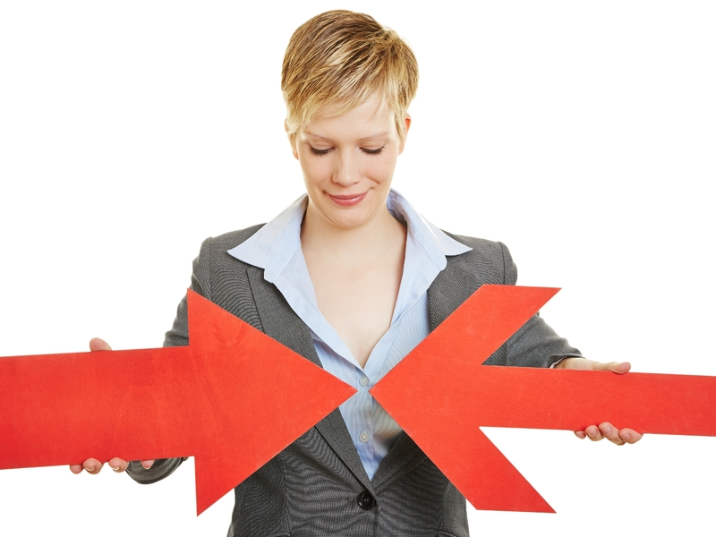 Une femme d'affaires faisant converger une flèche rouge, avec une autre flèche rouge plus large.