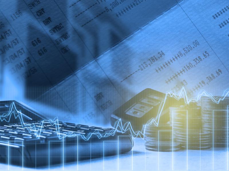 Une calculatrice et un tas de pièces sur une table. Devant un graphique financier qui monte et descend, derrière des feuilles de chiffres.